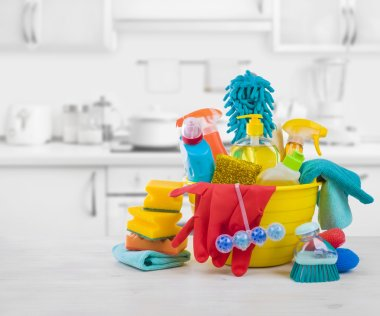 Various colorful cleaning products on table over blurred kitchen background