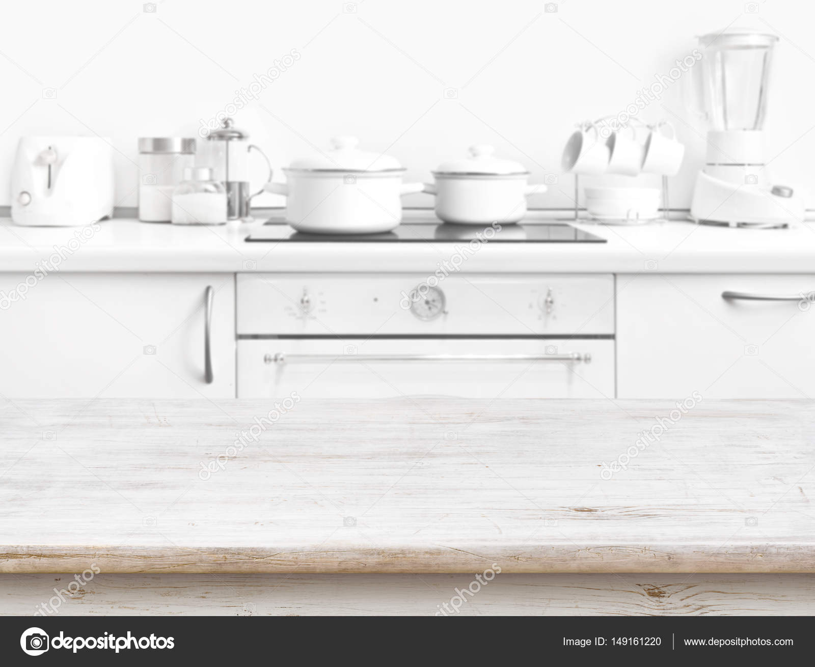 Wooden table in front of blurred white kitchen bench ...