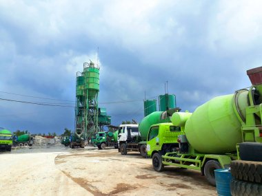 Green and white trucks and water tanks parked at construction workspace under blue sky