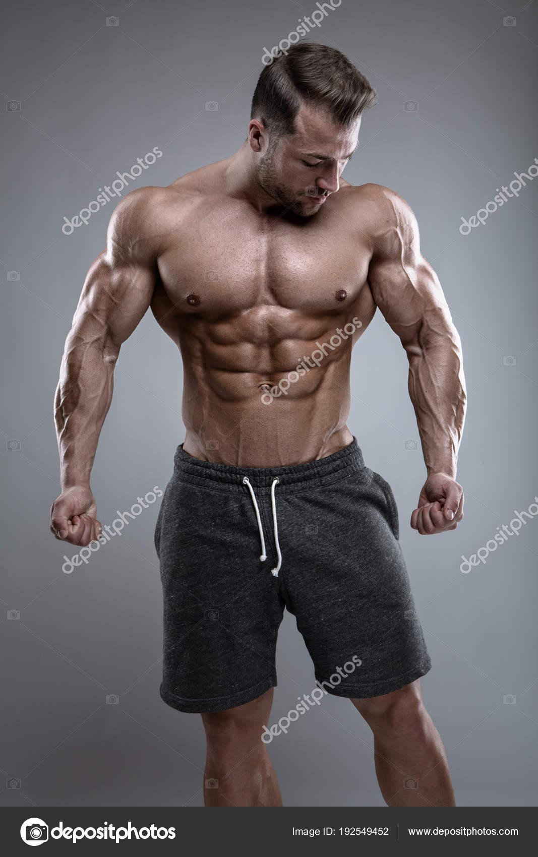 Starker athletischer Mann zeigt Körper und Bauchmuskeln