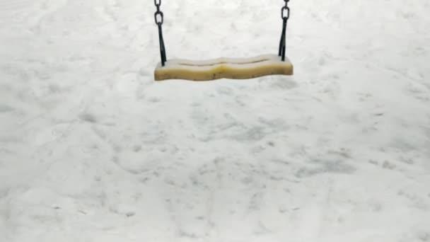 Schaukeln im Schnee ohne Menschen. Vor dem Hintergrund des Spielplatzes. Es gibt niemanden, der Wind bewegt die Schaukel.