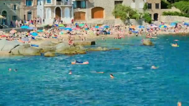 Holiday on the Beach in Spain in Summer. Typical Mediterranean beach in Summer day. People on vacation at the beach time lapse. Turquoise clear waters during leisure time on the seaside. Holidays scene on the beach. Having sunbath scene.