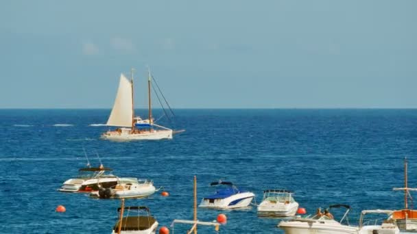 Sailboat Sailing in Crystal Clear Waters. Sailing and anchored boats in the Mediterranean sea. Wooden traditional boats and modern ships. Sunny day sailing the ocean with crystal waters.