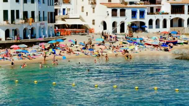Holiday on the Beach in Spain in Summer. Typical Mediterranean beach in Summer day. People on vacation at the beach view. Turquoise clear waters during leisure time on the seaside. Holidays scene on the beach. Having sunbath scene.