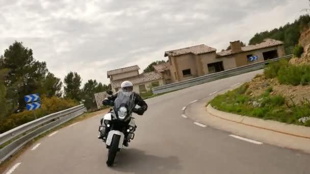 Motocyklista jízdě svůj sportovní motocykl na silnici křivky. Steady cam záběr mladého muže s jeho motorka enduro na jaře. Čelní pohled na kříž motocyklu v akci na malebné silnici v Katalánsku.