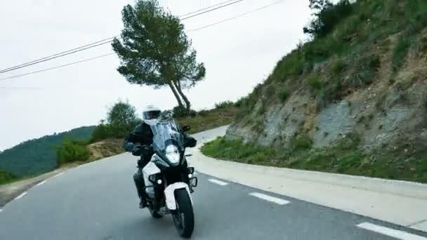 Motocyklista jízdě svůj sportovní motocykl na silnici křivky. Steady cam záběr mladého muže s jeho motorka enduro na jaře. Čelní pohled na kříž motocyklu v akci na malebné silnici v Katalánsku