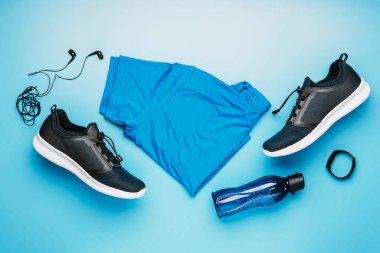 Flatlay blue clothing for running or crossfit, headphones, fitness bracelet, water bottle, shorts and t-shirt on a blue background, the idea of a healthy lifestyle ,top view