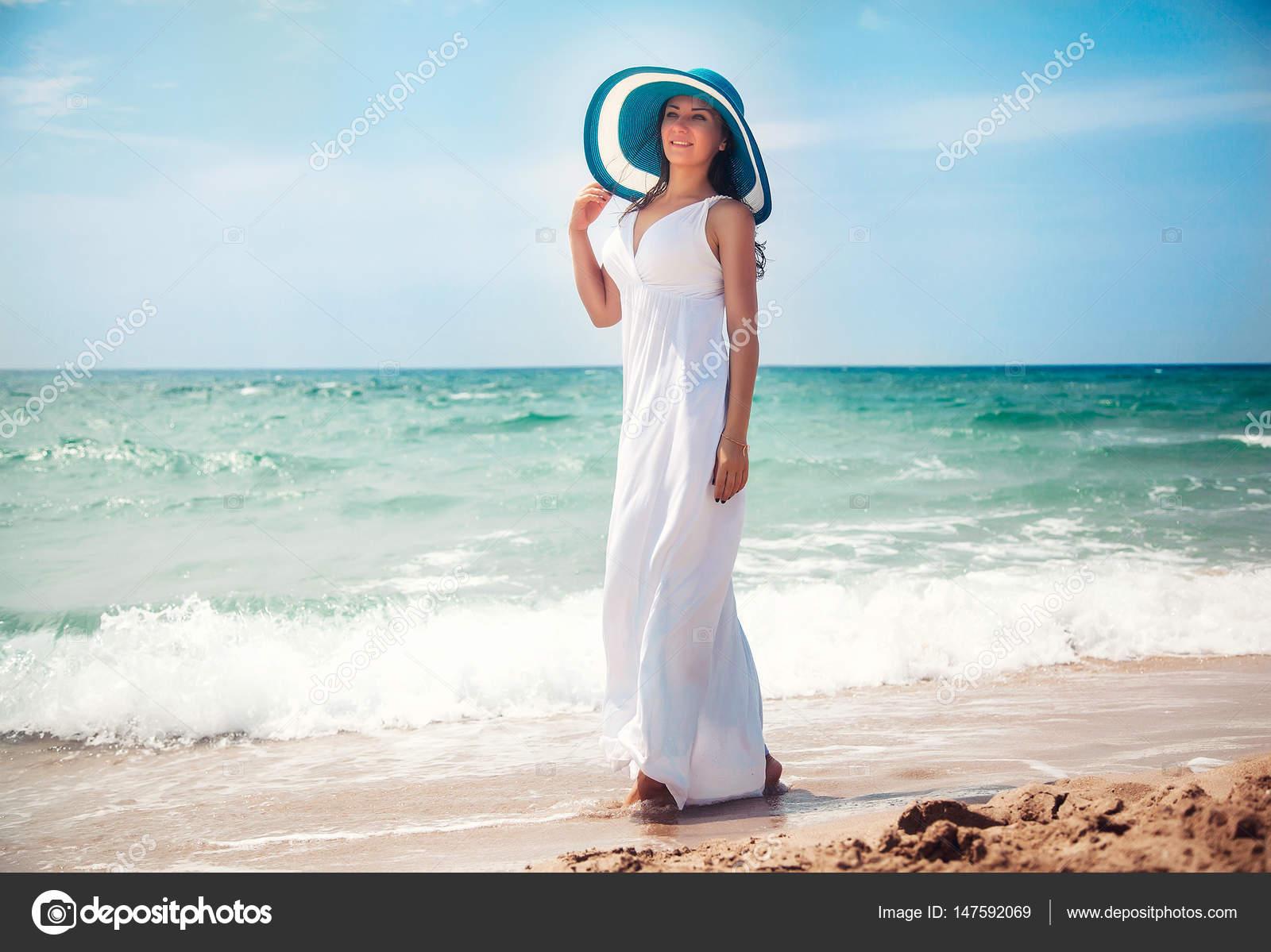 Hermosa mujer joven caminando por la playa con vestido largo