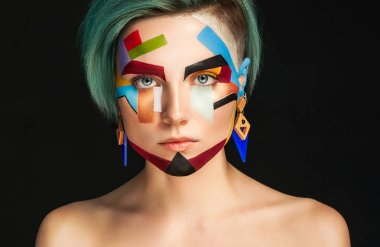 Art make up. Beautiful woman with creative make up over bblue ba