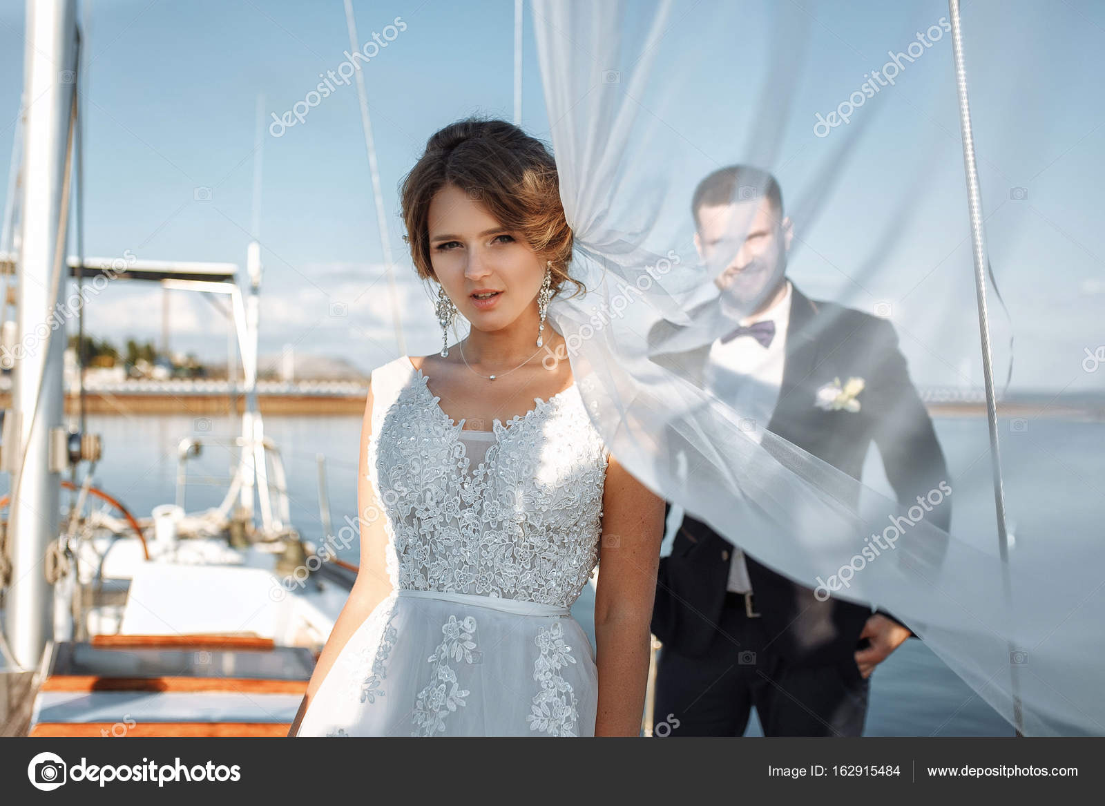 Wedding couple is hugging on a yacht. Beauty bride with groom. B ...