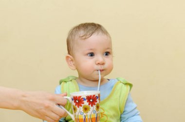 Baby drinks juice through a straw