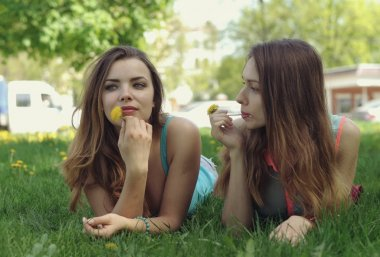 Two girlfriends lie on a green lawn