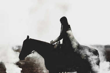 Beautiful silhouette of a girl who rides a horse through the thick smoke on a white background