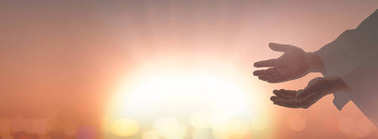 Easter sunday concept: Silhouette Jesus Christ open spiritual hands over blurred sunset background.