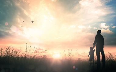 International migrants day concept: Silhouettes father and son holding hand in hand on meadow autumn sunset background.