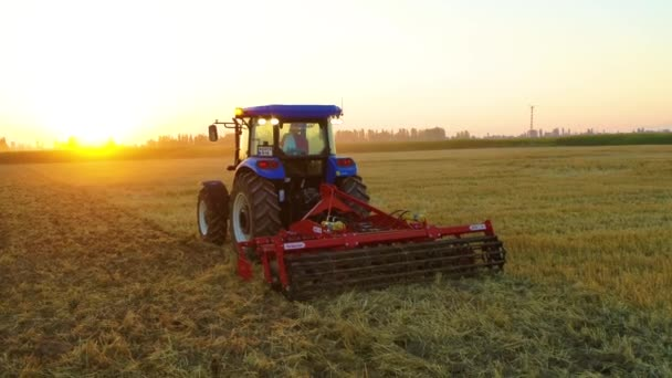 agricultural machine and tractor working in field and making tillage, cultivating from night to day