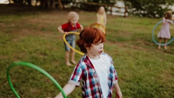 Rothaariger kleiner Junge mit Freunden, die Reifen am Zaun drehen. Langsames Filmmaterial
