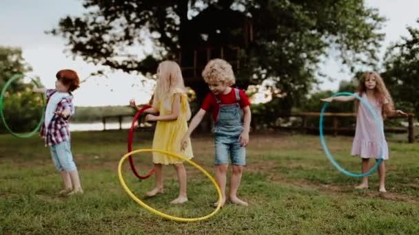 Geschwisterkinder drehen Reifen auf dem Rasen in der Nähe von Baumhäusern. Slo mo Filmmaterial
