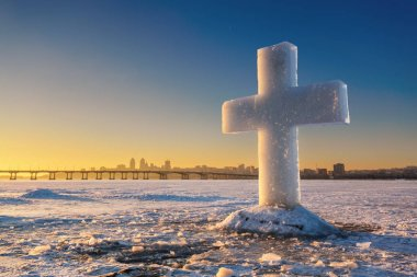 Beautiful winter landscape with Ice Cross on frozen river and sunset sky