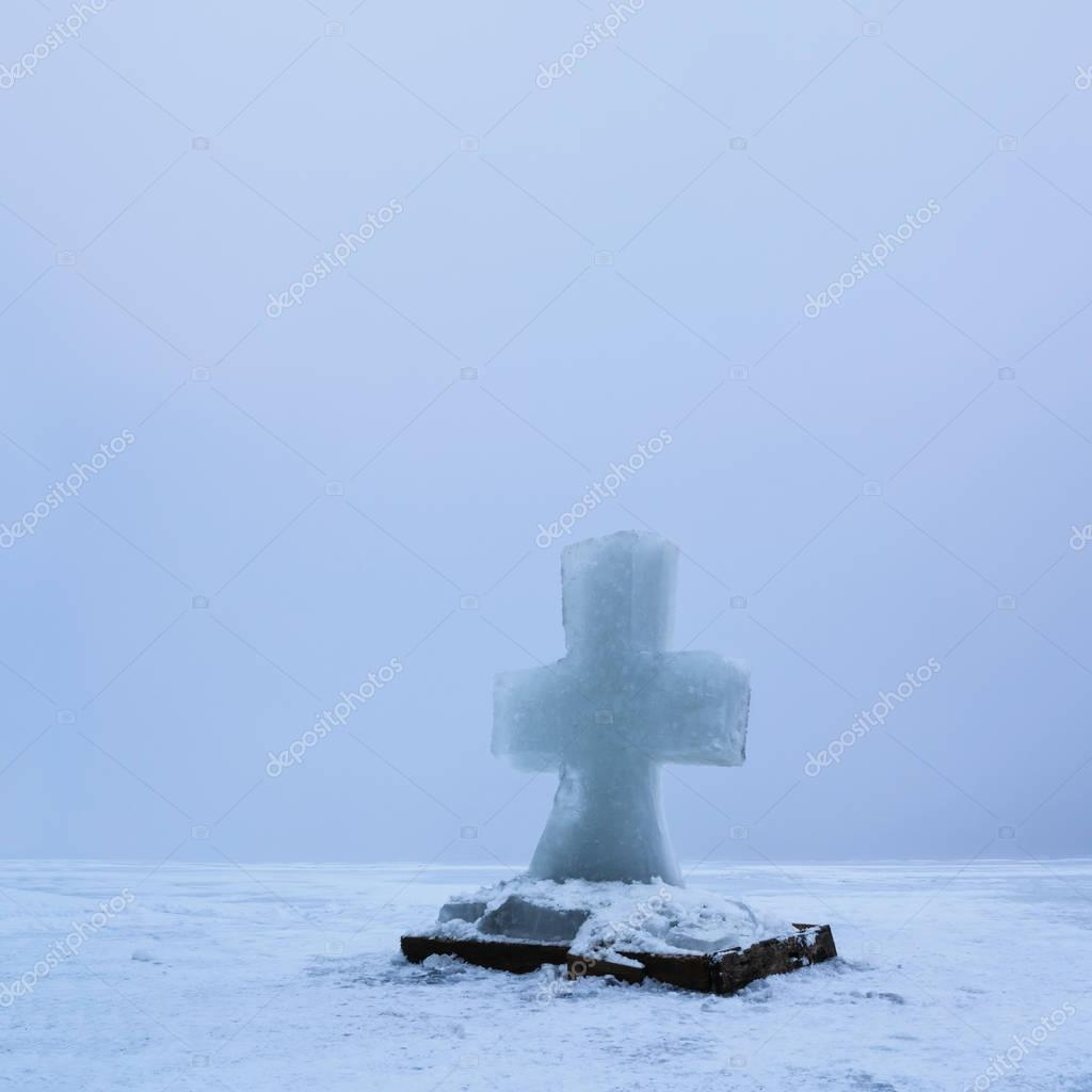 Beautiful winter landscape with Ice Cross on frozen river on foggy morning I