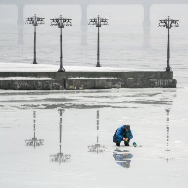 The fisherman is fishing on the ice of a frozen river in an early foggy morning II