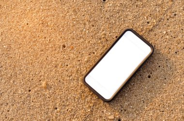 Smart phone on sand beach texture background. White copy space of technology and travel nature concept. Vintage tone filter color style.