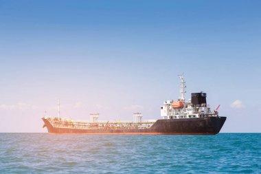Oil Ship tanker over sea coast skyline, with clear blue sky background