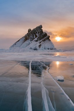 Ice water lake with rock peak mountain with sunset background, Baikal Russia winter season natural landscape