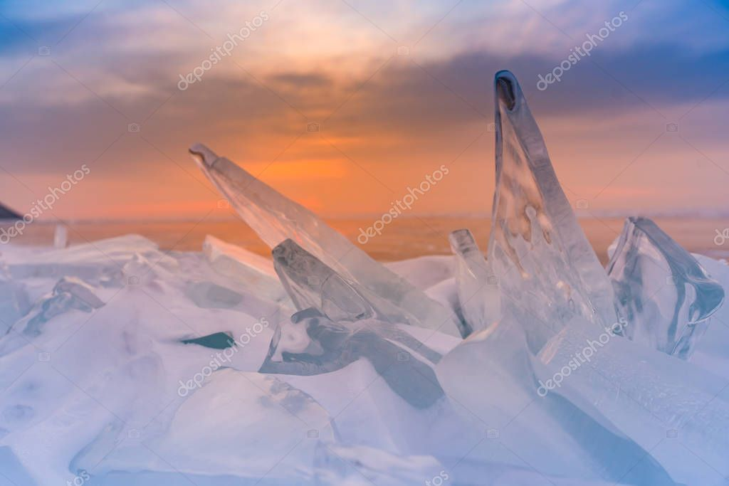 Sunset sky over Ice cracked in Baikal water lake, natural landscape background