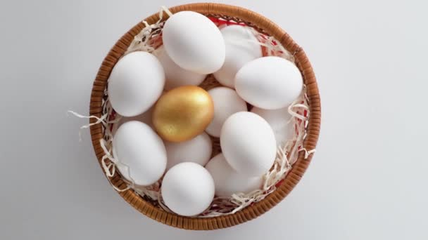 Close-up of a wicker basket lined with hay and filled with fresh and selected chicken eggs. White and a golden one.  Circle rotation. Top view.