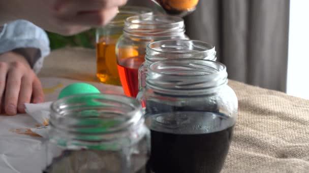 Eine Künstlerin taucht die Farbe Ostereier mit traditioneller Bienenwachs-Maltechnik auf den Hintergrund von Glascontainern mit Farbstoffen. Verwendung exquisiter und symbolischer ukrainischer Designmotive.