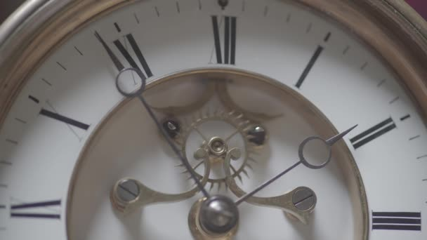 Macro shot of an antique vintage clock with a detailed depiction of the clock face, hands of the clock, cogwheel and pendulum.
