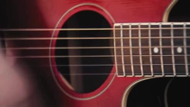 Blízký záběr ženy hrající venku na červenou kytaru.