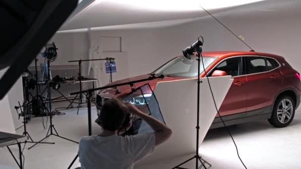 Široký záběr fotografa, jak fotí auto BMW X2 ve studiu.