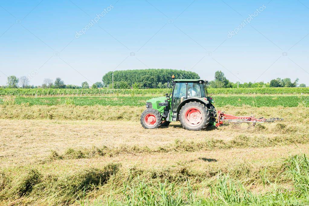 Agricultural landscape . Tractor haymaking