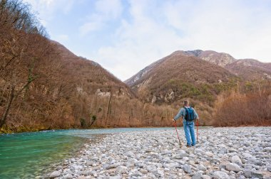 Hiker on the bank of a river. Walking toward mountain.