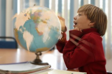 child in geography classes, is amazed to touch the globe with his finger, lights up or is destroyed. Teach to care for the planet