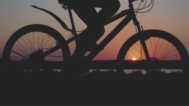 Fényképes közeli felvétel a kerékpáros kerekek és női lábak sziluettjéről, amint a városon kívül kerékpároznak tavasszal, miközben a naplemente sugaraiban gondoskodnak a környezetről.