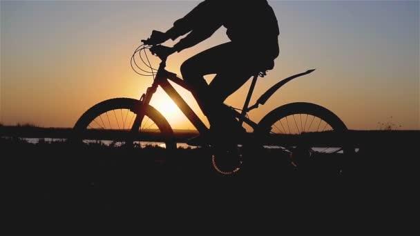 Krásná jarní nálada záběr mladé ženy nebo dívky na kole přes řeku pláž a šlapání ve večerním západu slunce světlo