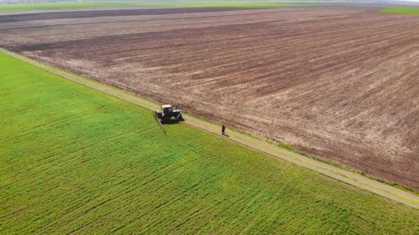 Letecký bezpilotní snímek zemědělce na traktoru s namontovaným postřikovačem s chemikáliemi uvnitř zatáčí na okraji pole s ječmenem nebo pšenicí
