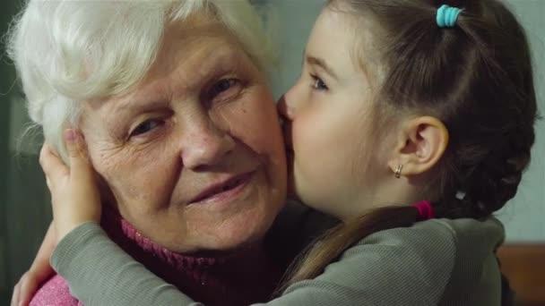 Roztomilá veselá vnučka líbá svou starší babičku na tvář mnohokrát. Mladá dívka se starou ženou. Teplé vztahy mezi dvěma generacemi
