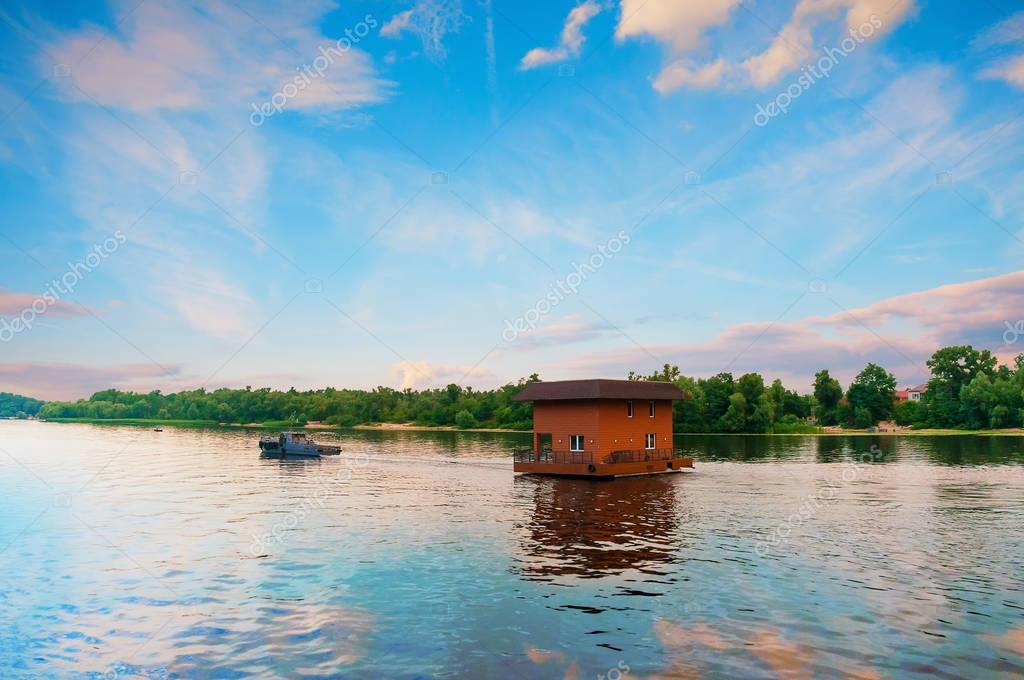 Tugboat towing house by river, Dnieper, Kiev, Ukraine