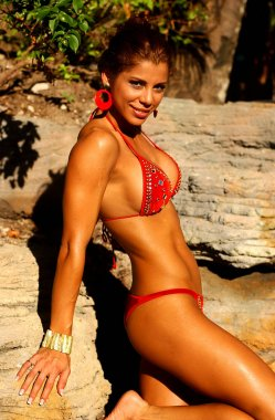Latin model poses in Bahamas - Cute String Bikini - Custom Leather Native Bikini Sultry sexy outfits with Stone Rock back ground copy space - Light makeup - Tight abs - Tight Butt - Reddish Tan Swimsuit - Light waterproof makeup  while smiling