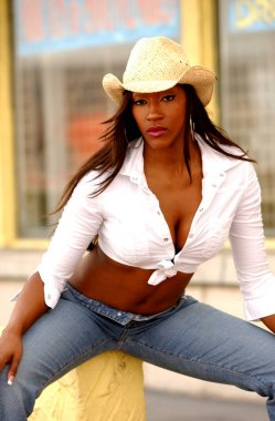 Cowgirl in cowboy hat blue jeans and white tie shirt posing sitting
