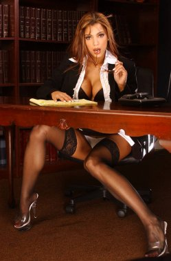 Unbelievably beautiful lawyer sitting in her office chair behind wooden desk in black thigh high stocking and heels on casual Friday