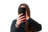 Asiatin nimmt ein Video mit ihrem Smartphone auf und bedeckt ihren Mund mit ihrer Hand vor Aufregung, isoliert auf weißem Hintergrund.