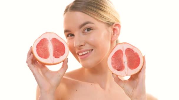 Žena držící dvě poloviny grapefruitu na bílém pozadí