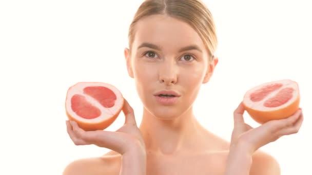 Roztomilá žena drží dvě poloviny grapefruitu na bílém pozadí