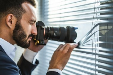 The businessman with a camera photographing through the blinds