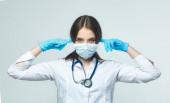Covid19, koronavírus, az egészségügy és az orvosok fogalma. Portré egy nő orvos, aki nem akar hallani.Felveszi az orvosi maszkot, hogy megakadályozzák a fertőzés a vírus